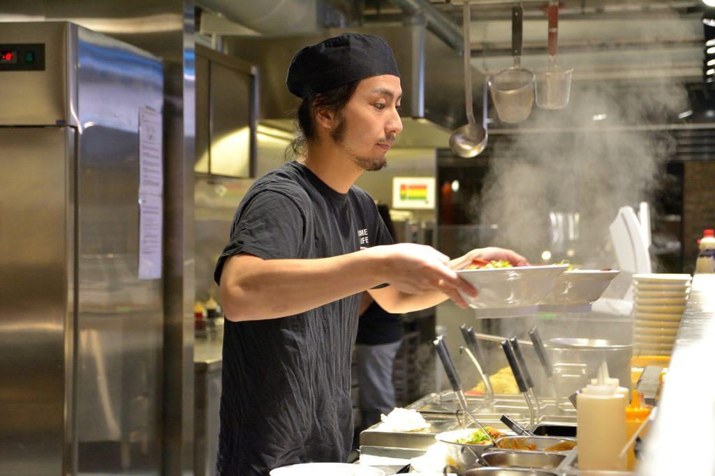 японский повар подает лапшу рамен